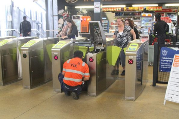 Vix technician fixing a defective myki gate at Sunshine station
