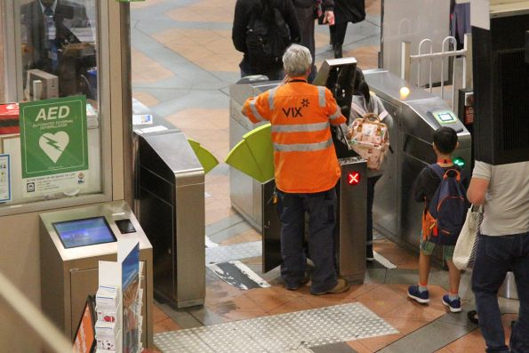 Vix staff fixing a defective myki gate at Flagstaff station