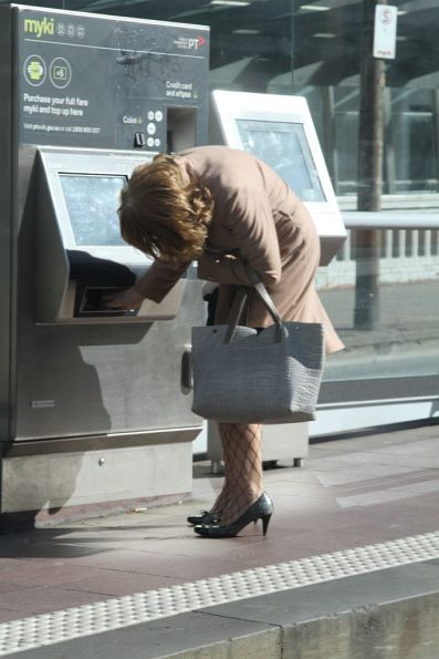 Leaning down to check the Myki machine for an unwanted receipt