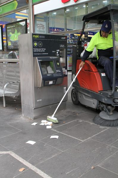 City of Melbourne street sweeper has to clean up the mess of abandoned myki receipts at a Swanston Street tram stop