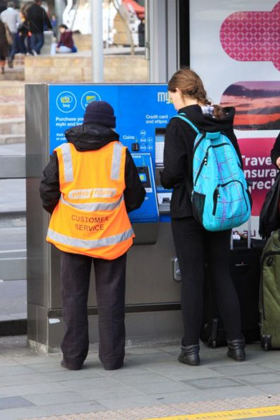 Yarra Trams customer service staff help out a tourist with the Myki machine outside Federation Square
