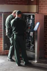 Armaguard staff empty a myki ticket machine