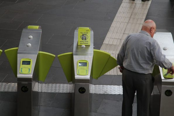 Cardboard 'You must touch on every time you board' signs affixed to the country barriers at Southern Cross Station