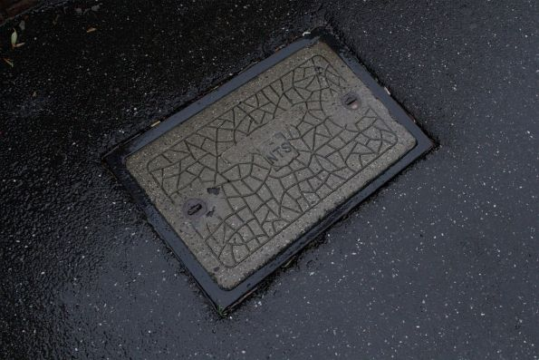 NTS (New Ticketing Solution) branded manhole cover at Kensington station