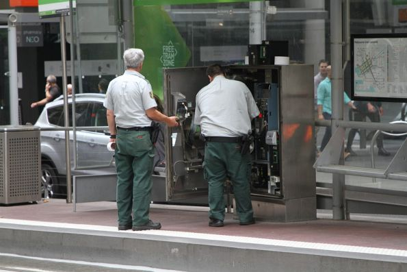 Armaguard staff empty the myki machine at the Bourke and William Street tram stop