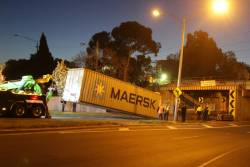 Tow truck drags the damaged container away from the bridge