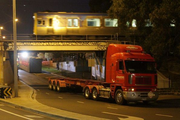 Offending truck and container cleared from under the bridge, as a Comeng train passes over the top