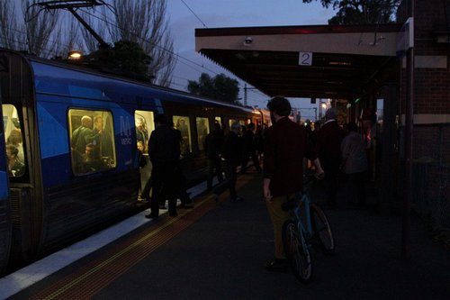 Passengers step onto a dark platform at Newmarket station