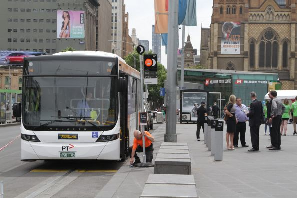 Staff remove the temporary bus stop flag from Federation Square