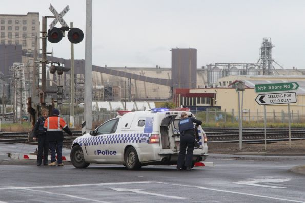 Police and V/Line staff inspect the downed boom barrier arm at Station Street, North Shore