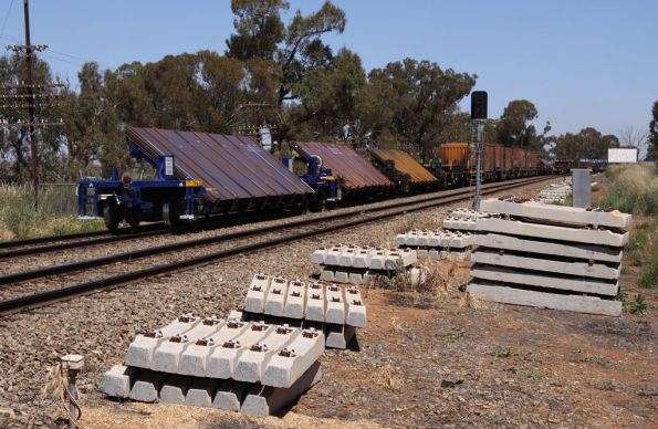 Tail end of the train passing a pile of new concrete sleepers at Marinna