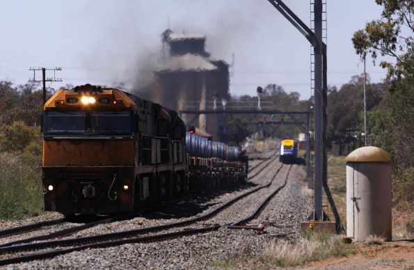 The steel train departs on the main line after the cross, the XPT stops at the platform on the loop road