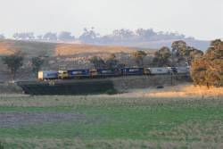 NR70 leads NR52 and NR45 on a southbound PN intermodal service passes the tail end of the up Harefield train at Jindalee
