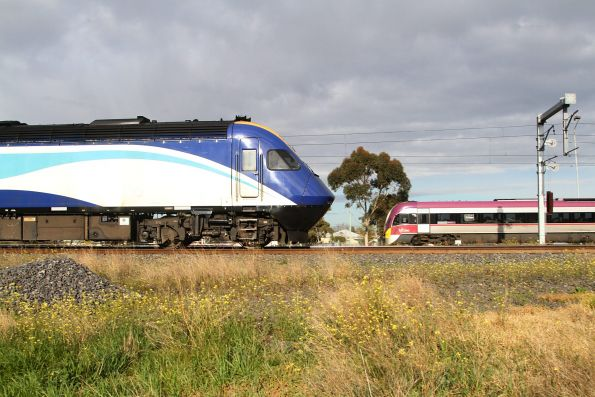 Northbound XPT passes a VLocity train at Sunshine