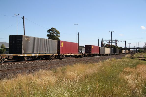 Handful of container wagons attached to the rear of an up steel train at McIntyre Loop