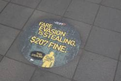 PTV 'Fare Evasion is Stealing' advertisment on the pavement at a tram stop