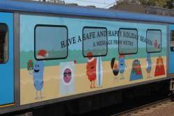 Christmas-themed 'Dumb Ways to Die' banner on the side of a Siemens train