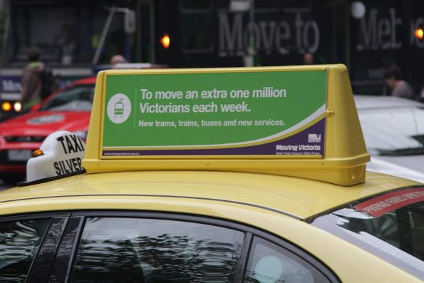 Poster for the Liberal Government's 'Moving Victoria' campaign on a taxi roof