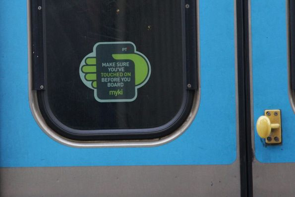 'Make sure you've touched on before you board' sticker facing the outside of a Comeng train door