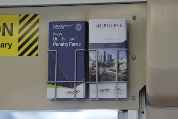 'New On-the-top Penalty Fares' brochure onboard a tram beside a 'Discover Melbourne' visitor map