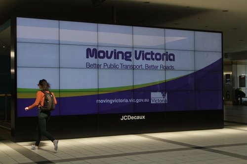 'Moving Victoria' propaganda among the advertisements on the big screen at Flinders Street Station