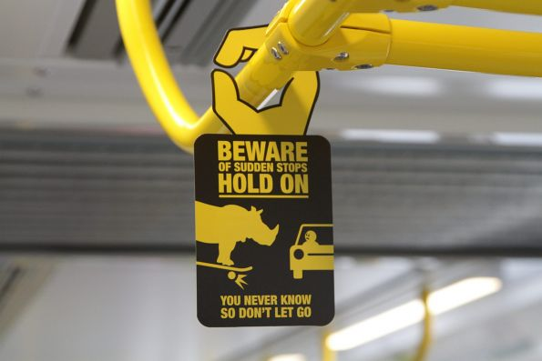 'Beware of sudden stops - hold on' flyer hanging from a tram grab rail