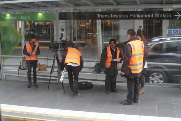 Yarra Trams staff filming at the Town Hall tram stop on Collins Street
