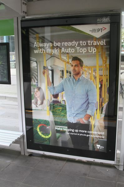 'Always be ready to travel with myki Auto Top Up' poster at a Melbourne CBD tram stop