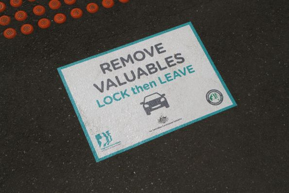Neighbourhood Watch 'Remove valuables: lock then leave' signage on the floor at a station entrance