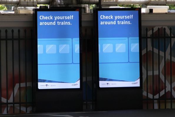 'Check yourself around trains' campaign video on the screens at Flinders Street Station