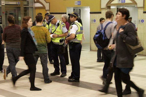 Protective Services Officers at Flinders Street Station write down a passenger's details
