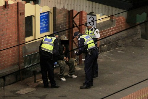 Two Protective Services Officers and a Victoria Police officer question a passenger at Footscray station