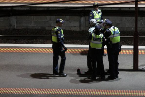 An uppity passenger restrained by a group of Protective Services Officers