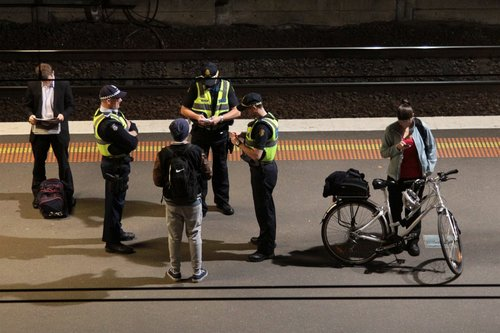 Two PSOs question a passenger, while a Victoria Police officer supervises