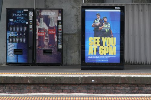 'See you at 6pm' billboard at North Melbourne station