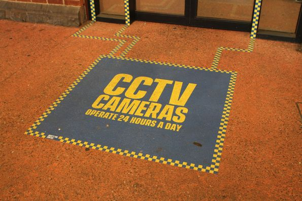 'CCTV cameras operate 24 hours a day' sticker on the concourse floor at Footscray station
