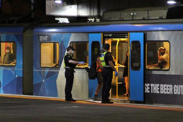 Protective Services Officers talk to a passenger onboard a train at Sunshine