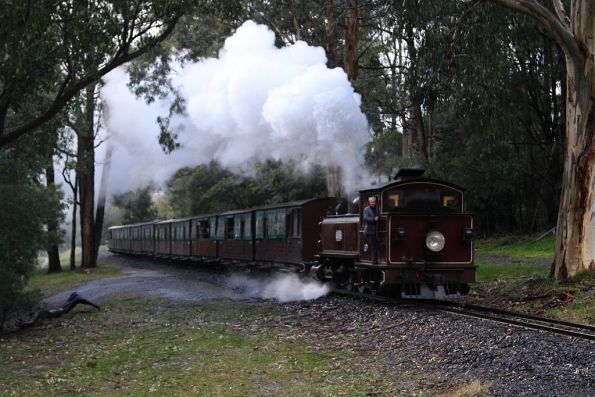 12NA leads the train towards the Belgrave-Gembrook Road level crossing in Menzies Creek
