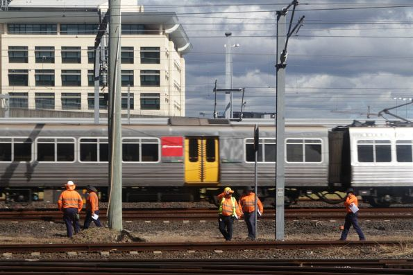 Suburban train passes track workers at Roma Street station