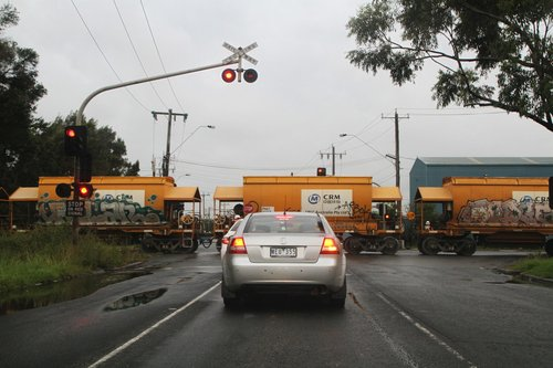Traffic controllers with STOP signs guard the Somerville Road level crossing at Brooklyn