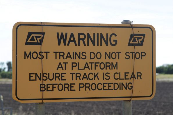 'Most trains do not stop at platform' warning sign at a level crossing adjacent to Bowen station