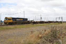 NR19 leads a rake of empty rail wagons from Anzac Sidings back to Dynon