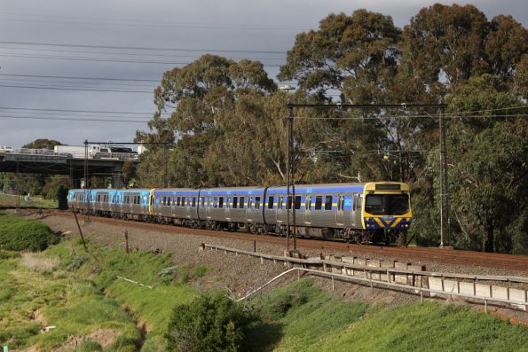 EDI Comeng 353M leads a mixed liveried set on the up at Yarraville