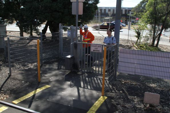 Safeworking staff watch over the down end pedestrian crossing at Reservoir