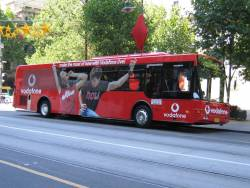 'Vodafone Live' promotional bus MO8333 parked outside City Square on Swanston Street