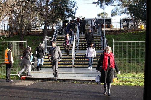 Passengers head down to the Flemington Racecourse platform from the bus interchange