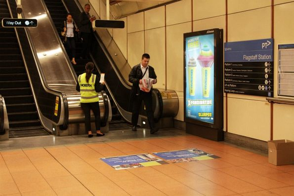 Temporary staff hand out RRL bus replacement flyers at Flagstaff station during evening peak