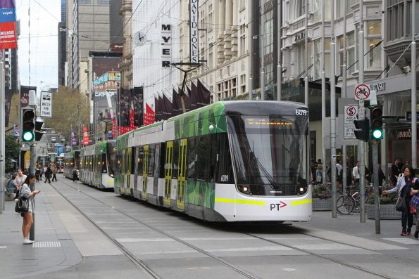 E.6019 leads a queue of trams waiting to head east at Bourke and Swanston Street
