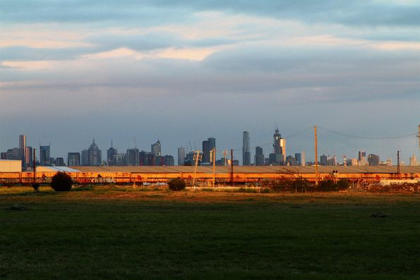 Melbourne CBD skyline in the background, as SCT's 7MB9 service heads north through Brooklyn