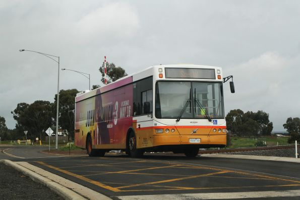 Sita bus #100 7928AO crosses the Coburns Road level crossing in Melton